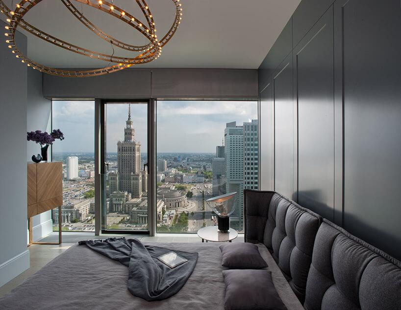 elegancka sypialnia zdużym łóżkiem na tle panoramicznego okna zwidokiem na płac kultury