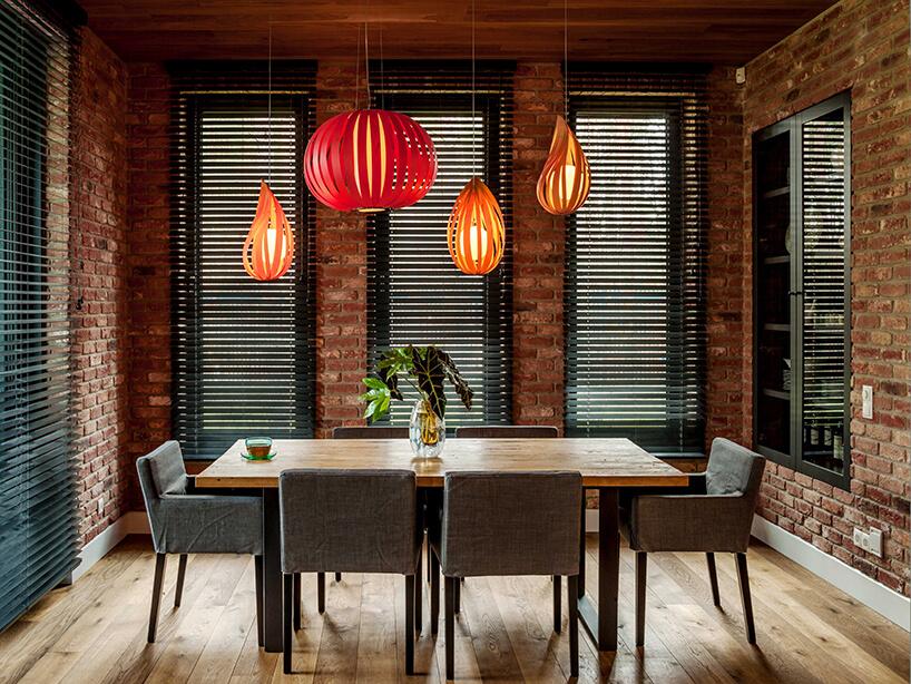 mała jadalnia zceglanymi ścianami zwysokimi wąskim oknami zczarnymi drewnianymi żaluzjami wewnętrznymi zdrewnianym stołem pod czerwonymi lampami