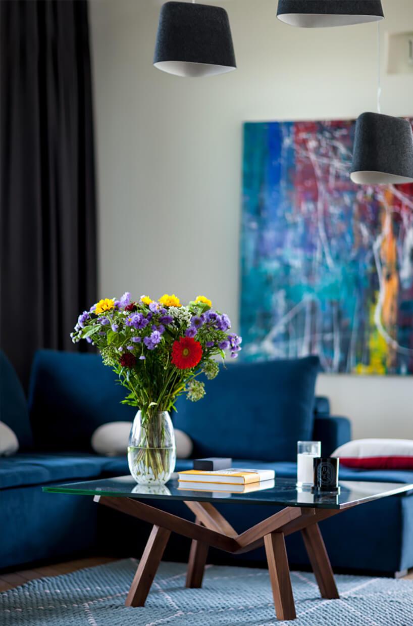elegancki salon zciemno niebieską sofa narożną jako tło dla niskiego stolika na drewnianym stelażu ze szklanym blatem