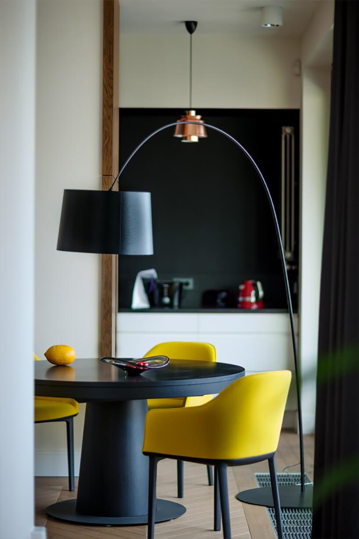 jasne wnętrze zczarnym okrągłym stołem zżółtymi krzesłami na czarnych nogach