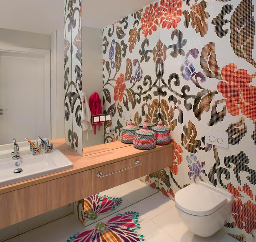 biała łazienka wmozaikową kolorową ścianę ipodłoge zmotywem roślinnym imotylem