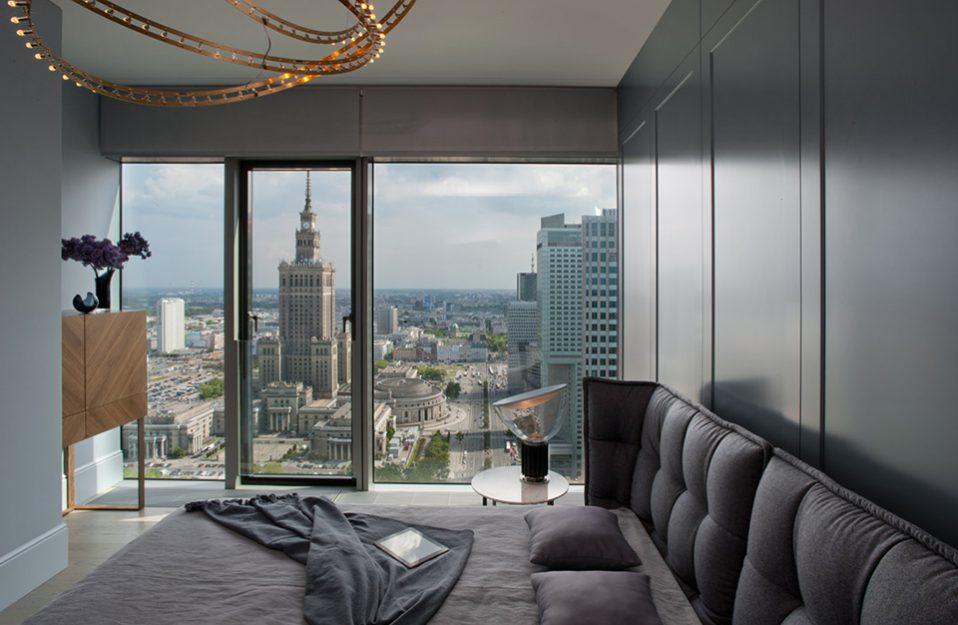 elegancka sypialnia z dużym łóżkiem na tle panoramicznego okna z widokiem na płac kultury