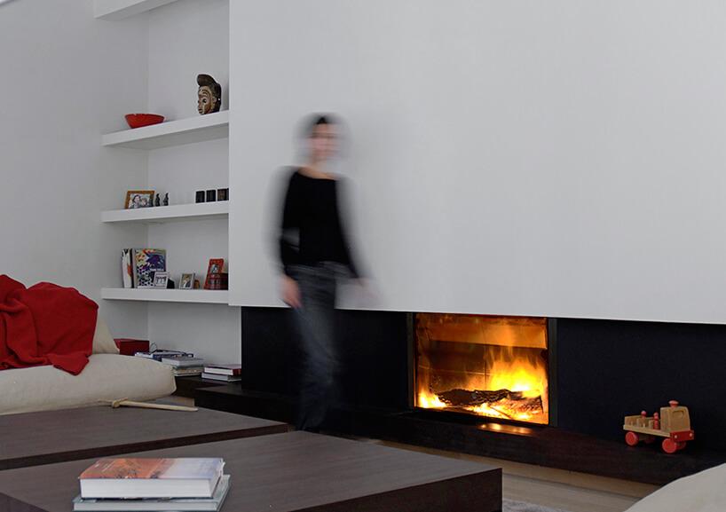 nowoczesny kominek Stuv 21 od Stuv wniższej czarnej zabudowie pod białą zabudową wnowoczesnym salonie