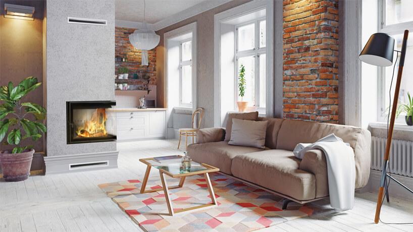 nowoczesny kominek narożny Lucy od Kratki wszarej zabudowie zkawalerce zbiała drewnianą podłogą zaneksem kuchennym zceglanymi filarami za beżową sofą