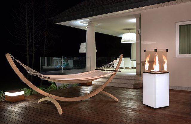 elegancki zewnętrzny kominek gazowy od Kratki na białej podstawie na drewnianym wieczornym tarasie obok hamaka