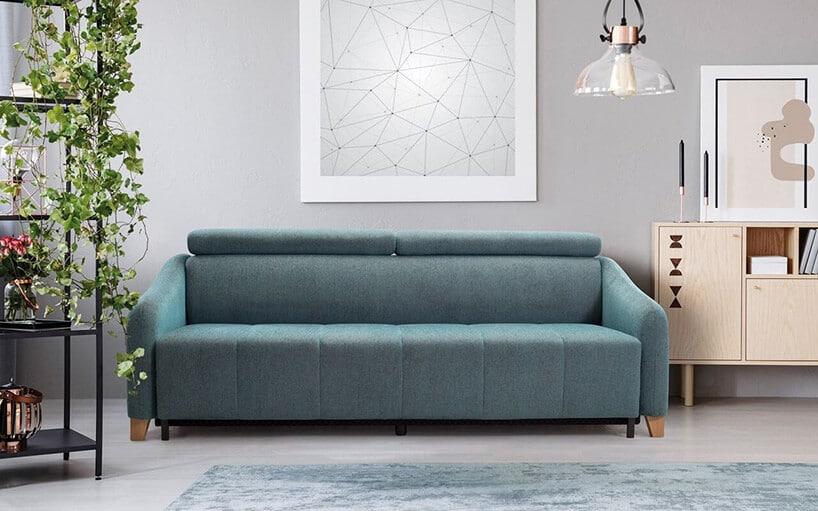 jasno niebieska kanapa wszarym pomieszczeniu zdywanem