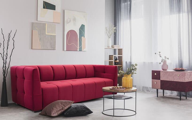czerwona wąska kanapa wmałym mieszkaniu