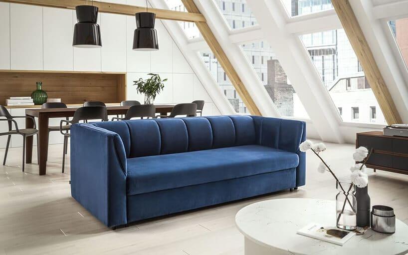 ciemno niebieska kanapa na białej podłodze przy drewnianym stole