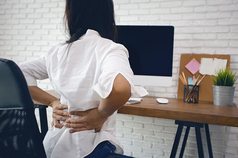 kobieta siedząca na krześle itrzymająca się za plecy przy drewnianym biurku
