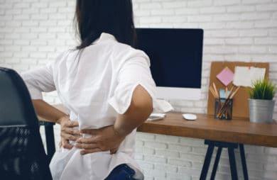 kobieta siedząca na krześle i trzymająca się za plecy przy drewnianym biurku