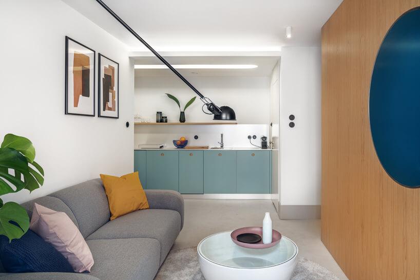 projekt nowoczesnego małego wnętrza zszarą sofą imałym białym stolikiem