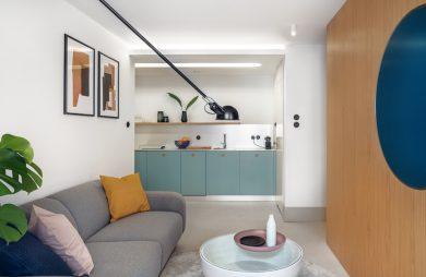 projekt nowoczesnego małego wnętrza z szarą sofą i małym białym stolikiem
