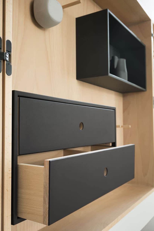 drewniana zabudowa zczarnymi szufladami iczarną szafką