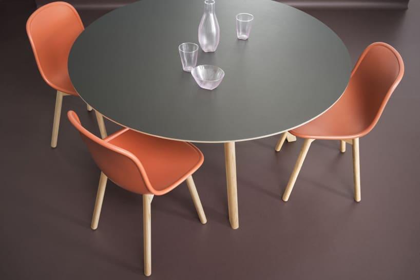 szary drewniany okrągły stół ztrzema drewnianymi krzesłami zpomarańczowym siedziskiem