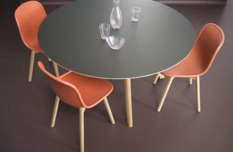 szary drewniany okrągły stół z trzema drewnianymi krzesłami z pomarańczowym siedziskiem