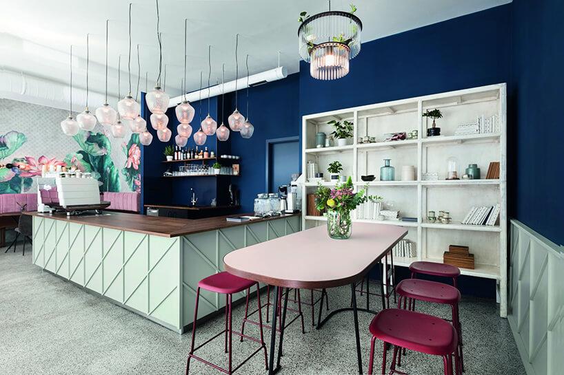 przytulne wnętrze restauracji wpastelowych kolorach zdwoma ścianami wciemnym niebieskim kolorze