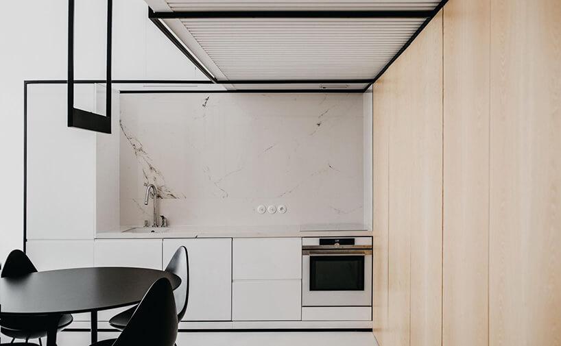 małe wnętrze zbiałym aneksem kuchennym pod czarną antresolą zbiałym łóżkiem