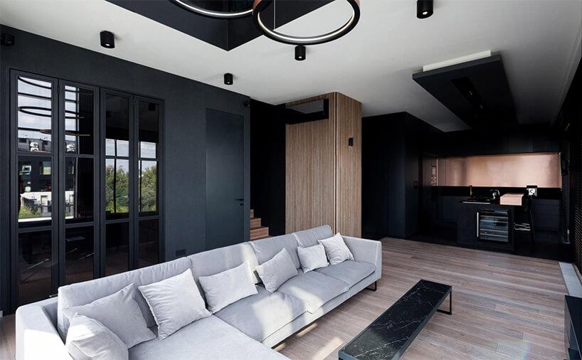 czarne wnętrze zbiałym sufitem zdużą szara narożną sofą