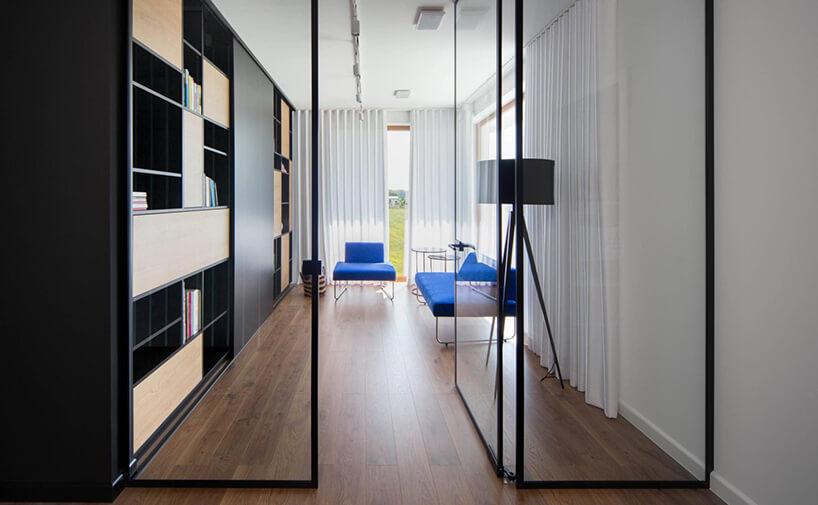 pokój zciemną drewnianą podłogą zprzeszkloną ścianą wejściową zniebieską sofą ifotelem