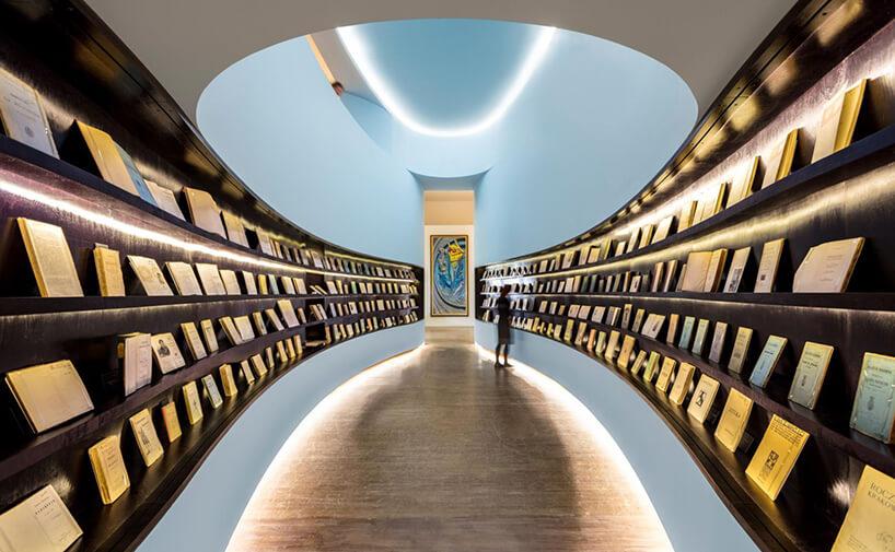 owalna przestrzeń zciemnymi półkami do ekspozycji książek zniebieskim przewężeniem pod sufitem