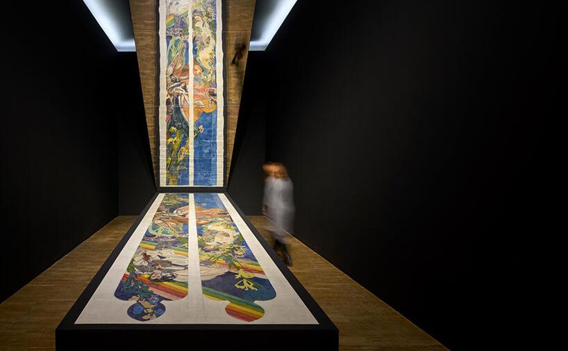ciemne wnętrze ekspozycyjne zjasną drewnianą podłogą ipochylonym lustrem nad ekspozycją