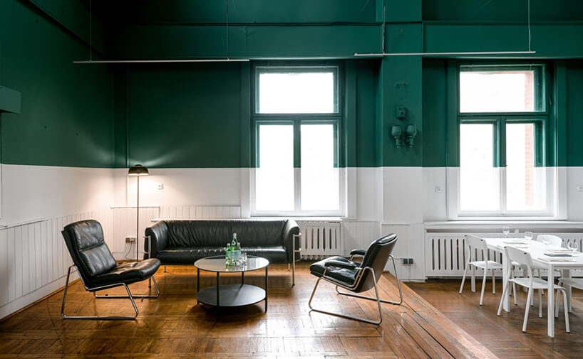 otwarte wnętrze zdrewnianą parkietową podłogą pod ścianami zbiałym pasem do połowy ściany izielonym wgórę jako tło dla skórzanego zestawu sofy zdwoma fotelami na chromowanych nogach