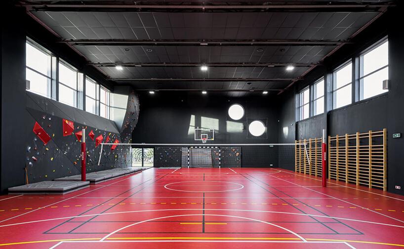 czarna sala gimnastyczna zczerwoną nawierzchnią na podłodze ze ścianką wspinaczkową