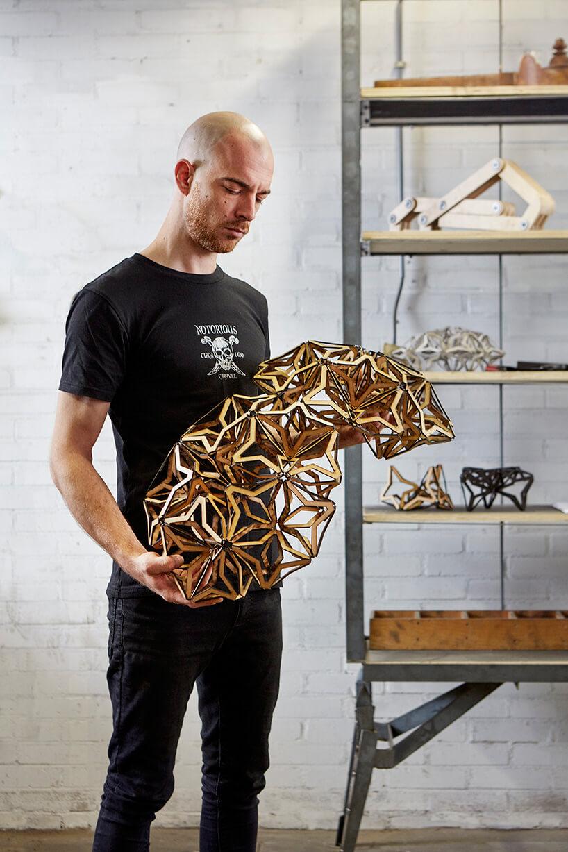 twórca trzymający część abażurowej lampy