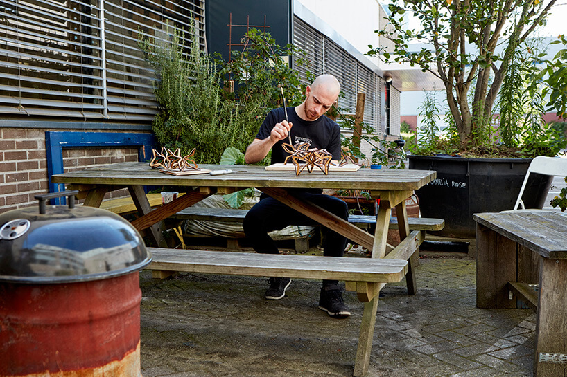 twórca siedzący na ławce podczas pracy nad lampą
