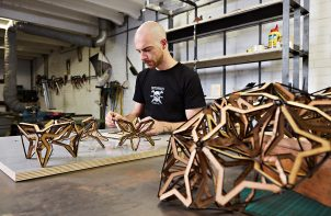 twórca podczas pracy nad drewnianą lampą