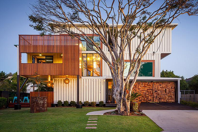 piętrowy dom zkontenerów zdużym drzewem