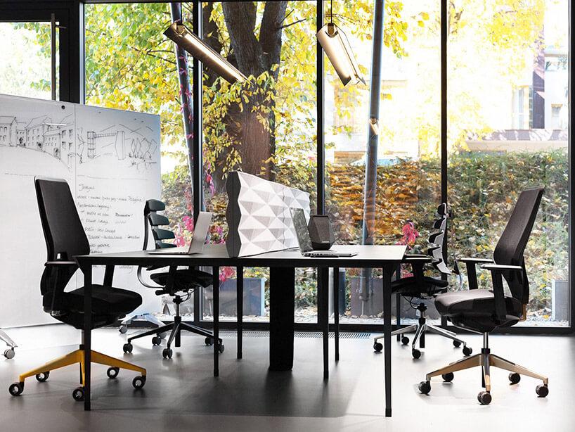 dwa biurka zkrzesłami na tle przeszklonej ściany
