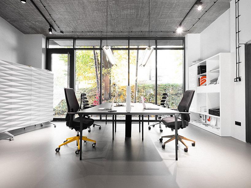 dwa biurka zkrzesłami wbiałym biurze na tle przeszklonej ściany