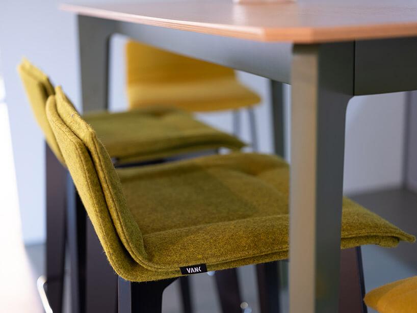 krzesła zżółtym siedziskiem wsunięte pod stół