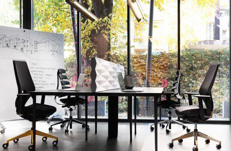 dwa biurka z krzesłami na tle przeszklonej ściany