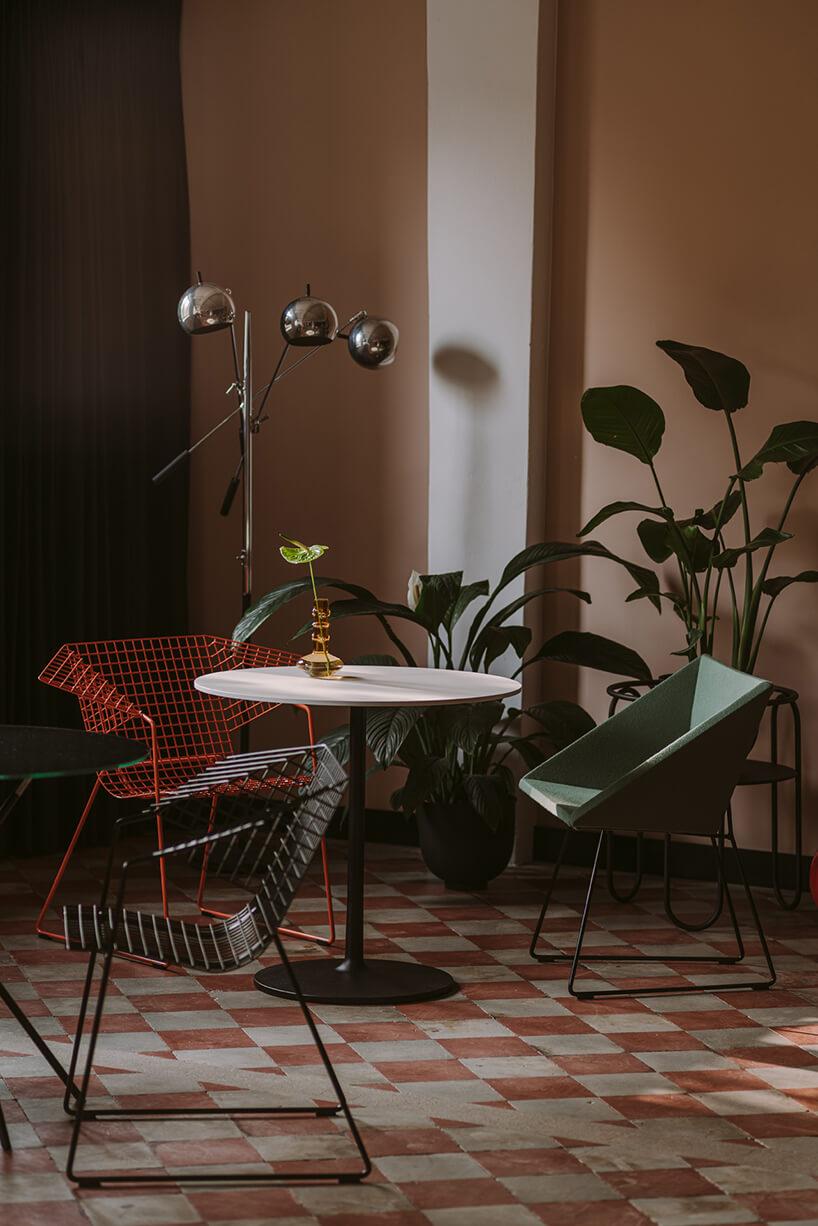 trzy klasyczne krzesła wczerwonym czarnym izielonym kolorze przy małych owalnych biurkach wkreatywnym wnętrzu CLAY.WARSAW