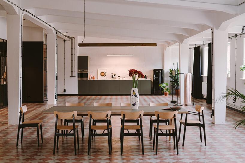 przestronne wnętrze jadalni zdużym stołem ikrzesłami na tle aneksu kuchennego wkreatywnym wnętrzu CLAY.WARSAW