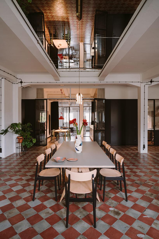 długi stół zkrzesłami na podłodze wbiało czerwone kwadraty pod lustrem nsuficie wkreatywnym wnętrzu CLAY.WARSAW