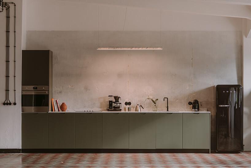 aneks kuchenny zzielonymi frontami szafek obok brązowej lodówki na tle starej ściany wkreatywnym wnętrzu CLAY.WARSAW