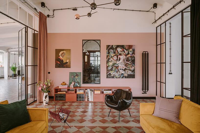 salon zdwoma żółtymi sofami iczarnym plastikowym fotelem wkreatywnym wnętrzu CLAY.WARSAW