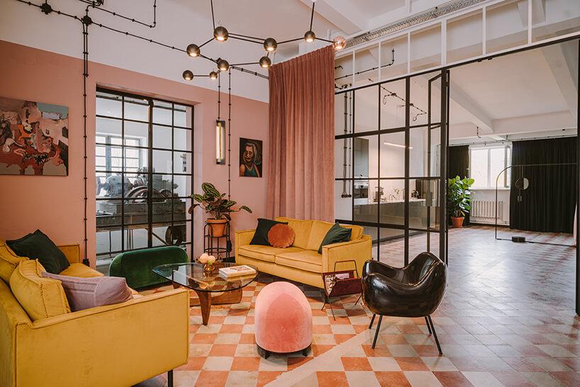salon zdwoma żółtymi sofami iczarnym plastikowym fotelem na tle przeszklonych drzwi wkreatywnym wnętrzu CLAY.WARSAW