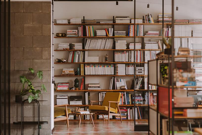 duży drewniany regał na książki pełen publikacji wkreatywnym wnętrzu CLAY.WARSAW