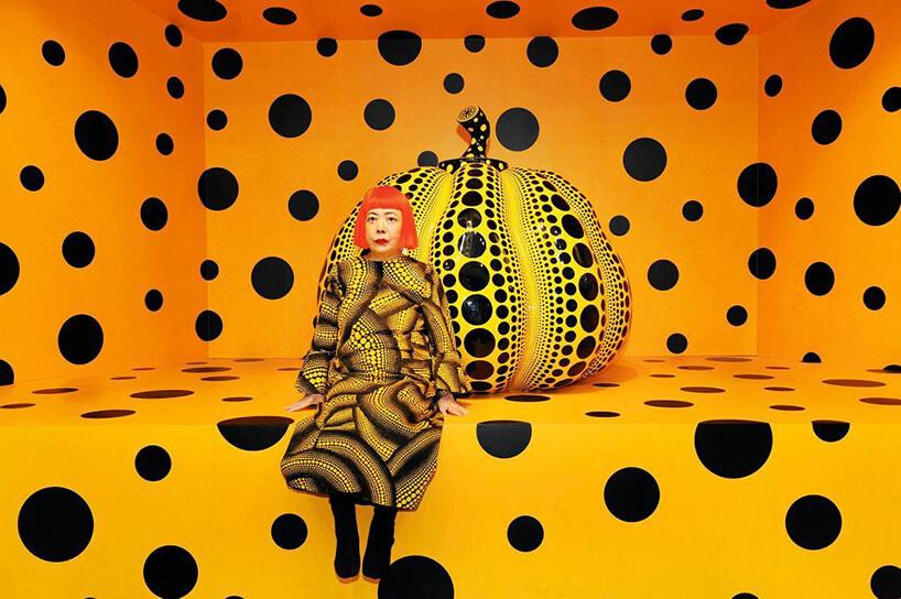 kobieta wżółto-czarnej sukience siedząca przed dynią wczarne kropki