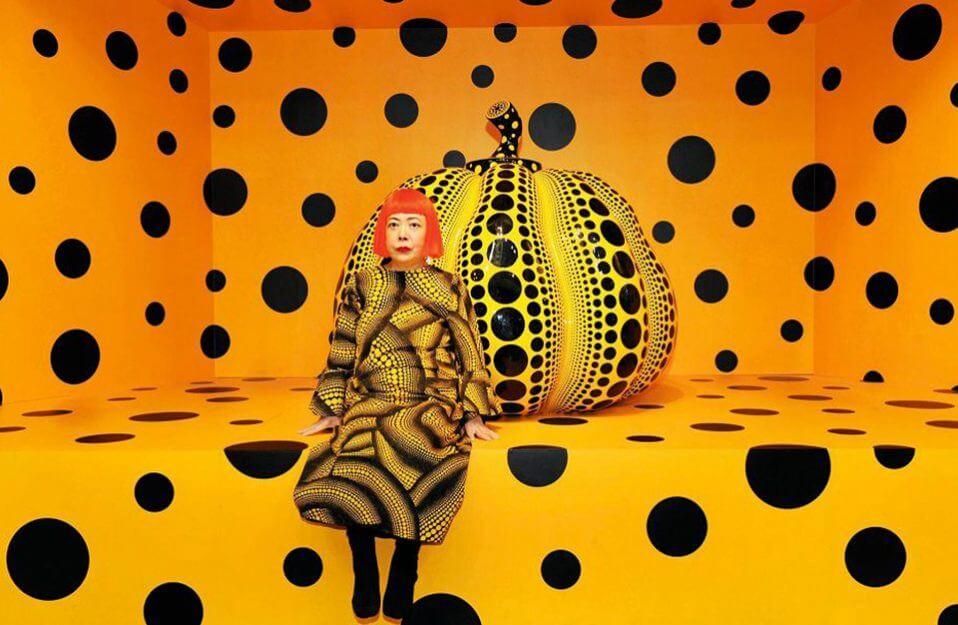 kobieta w żółto-czarnej sukience siedząca przed kropkowaną dynią
