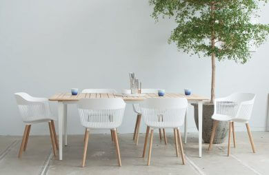 sześć białych krzeseł FRESH AIIR przy prostym drewnianym stole obok drzewka w doniczce