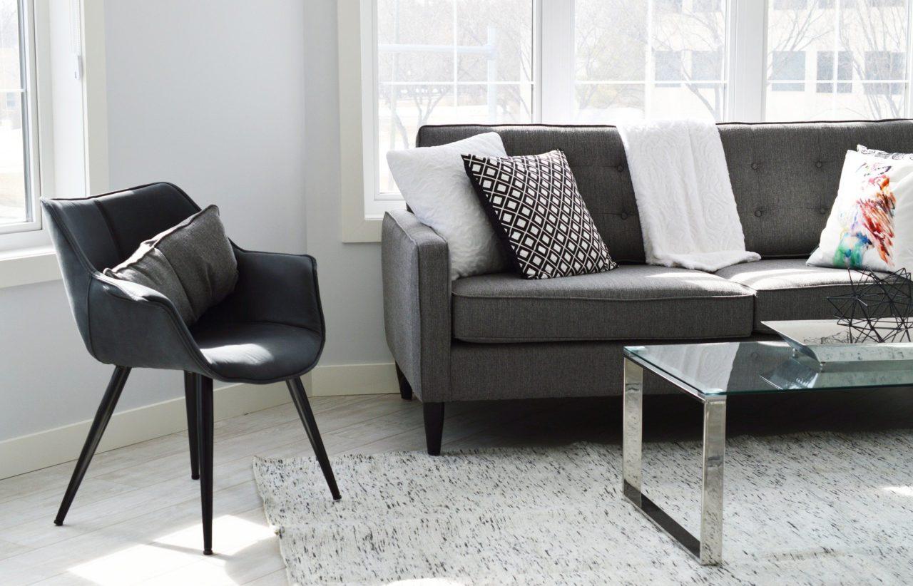 czarne nowoczesne krzesło wsalonie obok kanapy zpoduszkami
