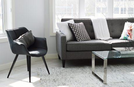 czarne krzesło w stonowanym salonie obok kanapy z poduszkami