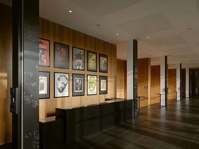 czarno biało brązowe wnętrze zkilkoma plakatami na ścianie zpodobizną Krzysztofa Pendereckiego projektu Nizio Design International