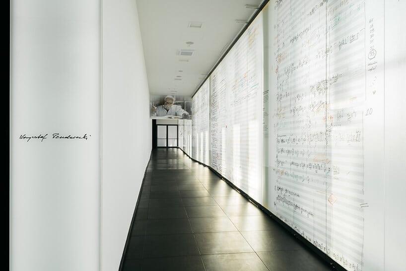 biały korytarz zczarną podłogą ze ścianą wyłożoną powiększonymi zapisami nutowymi Krzysztofa Pendereckiego projektu Nizio Design International