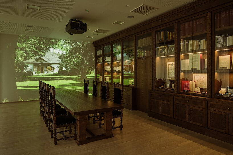 aranżacja zdużym stołem ikrzesłami epoki na tle ściany zgablotami wystawowymi obok ściany zprezentacją wideo projektu Nizio Design International